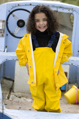 Smiling girl in waders on boat