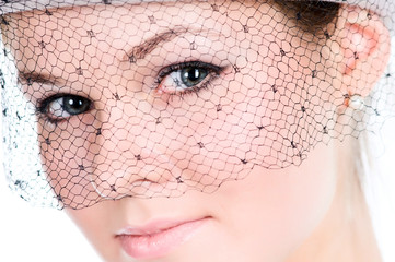 Closeup portrait of young lady in veil in high key