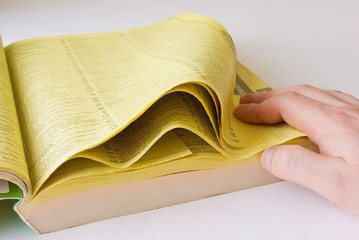 Listed yellow pages with hand