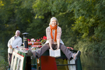 Happy woman holding book on narrow boat in canal