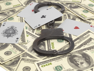 Handcuffs and aces on money background