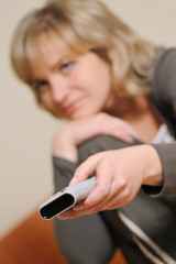 The woman with a television control panel. Selective focus