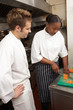 Chef Instructing Trainee In Restaurant Kitchen