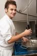Kitchen Worker Washing Up In Restaurant Kitchen
