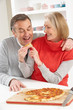 Senior Couple Sharing Takeaway Pizza In Kitchen