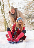 Fototapety Couple Sledging Through Snowy Woodland