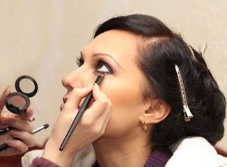 Professional make up artist applying make up on a teen model
