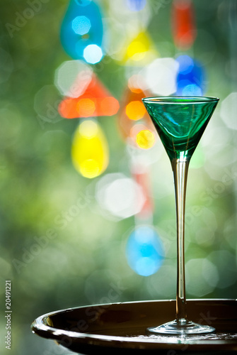 Green cocktail glass with colourful background
