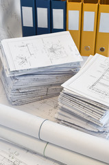 Heaps of design and project drawings and yellow folder.