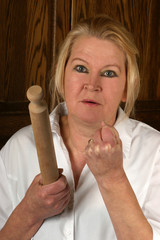 upset mature woman holds a rolling pin