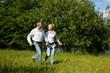 Älteres Paar läuft über eine Wiese