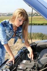 Blonde woman repairs car motor