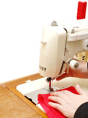 Sewing machine with red clothing, and the operator's hands