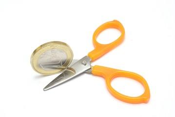 Forbice che taglia una moneta