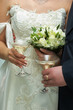 Hands of a newly-married couple with glasses of champagne and a