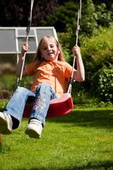 Kind auf der Schaukel im Garten