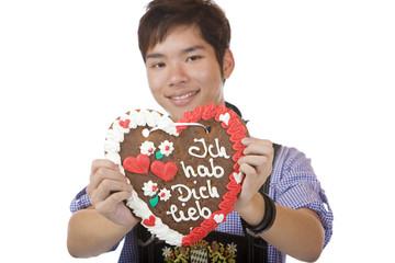 Happy man holding Oktoberfest gingerbread heart  - Lebkuchenherz
