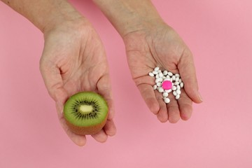 Mature woman hands and her choice -  pills or fruit
