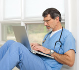 Doctor Reviewing and Researching on Laptop Computer poster