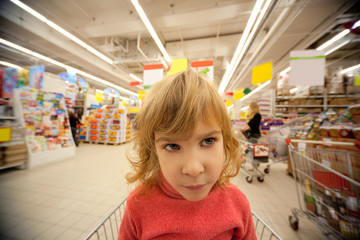 Small girl sit in shoppingcart in supermarket and look to right