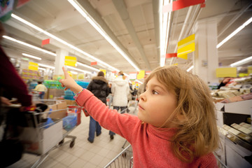 Small girl sit in shoppingcart in supermarket and show by finger