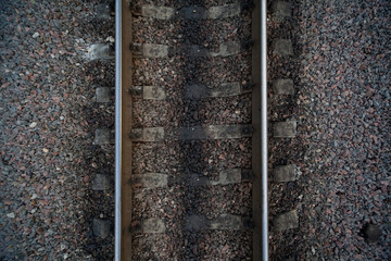 Rails and cross ties of railway among stones on centre
