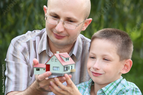 father and son keeping in their hands wendy house.