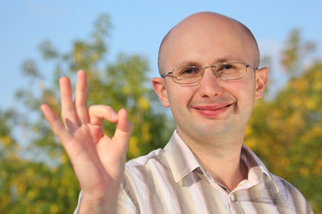 smiling man in early fall park with OK hand gesture