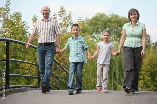 family with two children is walking on bridge in early fall park