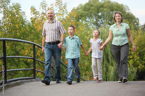 family is walking on bridge in early fall park