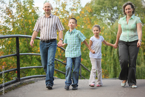 family with two children walking on bridge in early fall park