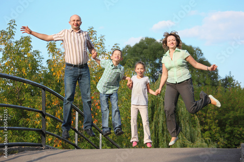 joyful family with two children is jumping on a bridge
