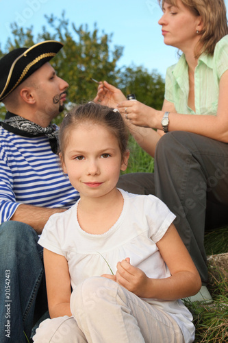 family in park. woman drawing whiskers and beard on man's face