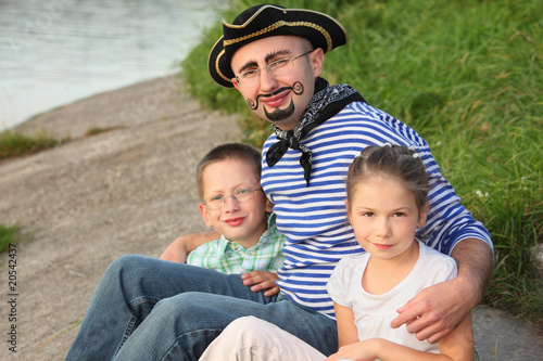 man in pirate suit with son and daughter near pond in fall park