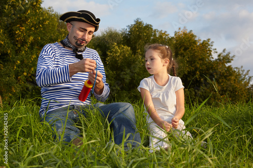 dad in pirate suit and daughter is sitting on grass.