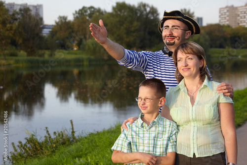 family in park near pond: man in pirate suit, woman and boy