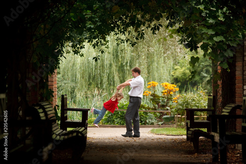 Father and daughter in summer garden  in plant tunnel.