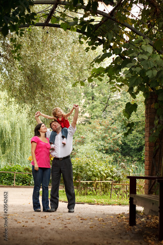 Family in summer garden. Girl sits at father on shoulders.