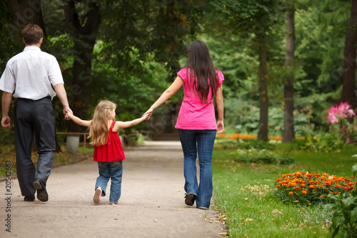 Parents together with daughter walk on summer garden.