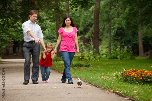 Parents together with daughter walk on summer garden