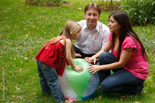 Parents with girl in garden. Play with big inflatable ball.