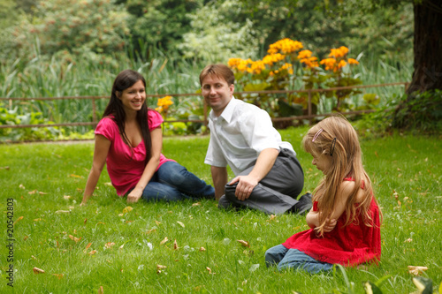 Parents together with little girl have rest in summer garden