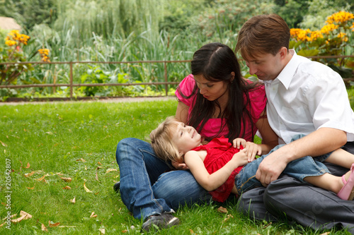 Parents together with little girl have rest in summer garden.