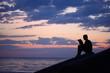 Silhouette guy sitting on breakwater in evening near sea, reads