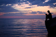 Silhouette guy with book sitting on breakwater near sea
