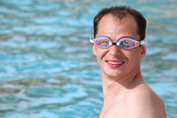 smiling young man in watersport goggles swimming in pool