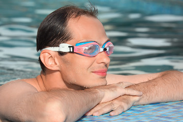 young man in watersport goggles swimming in pool, near ledge