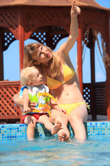 beautiful woman with blond little girl sitting on ledge pool