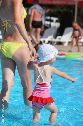 beautiful woman and little girl going on paddling pool