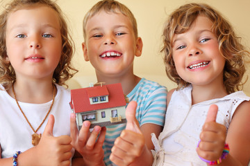 children three together keeping in hands model of house in cosy